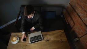 Affärsman som använder bärbara datorn i kafé- och innehavbitcoin i hand på den wood tabellen Top beskådar Tid schackningsperiod lager videofilmer