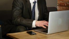 Affärsman som använder bärbara datorn i kafé på den wood tabellen stock video