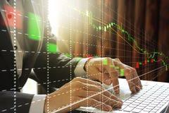 Affärsman som använder bärbara datorn med aktiemarknaden Fotografering för Bildbyråer