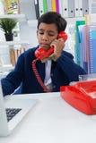 Affärsman som använder bärbara datorn, medan tala på landlinetelefonen royaltyfri fotografi