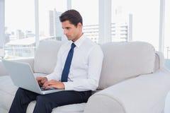 Affärsman som använder bärbara datorn på en soffa royaltyfri foto