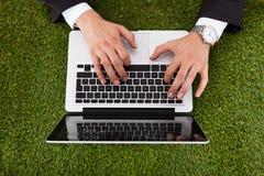 Affärsman som använder bärbara datorn på gräs Arkivfoto