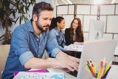 Affärsman som använder bärbara datorn på skrivbordet mot kvinnliga coworkers Arkivbild