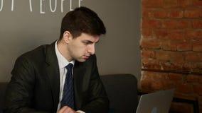 Affärsman som använder datoren i kafé stock video