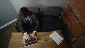 Affärsman som använder datoren i kafé på den wood tabellen Top beskådar arkivfilmer