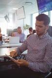 Affärsman som använder den digitala minnestavlan med kollegor som diskuterar i bakgrund royaltyfri fotografi