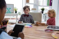 Affärsman som använder den digitala minnestavlan, medan diskutera med kollegor i regeringsställning Arkivfoto