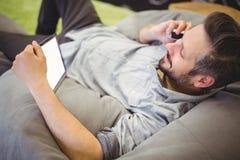 Affärsman som använder den digitala minnestavlan och mobiltelefonen, medan koppla av på bönapåse på det idérika kontoret Arkivfoton