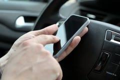 Affärsman som använder den smarta telefonen för mobil, medan köra bilen Fotografering för Bildbyråer