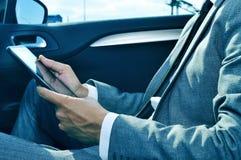 Affärsman som använder en minnestavla i en bil Arkivbild