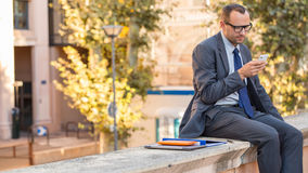 Affärsman som använder hans smarta telefon på en stadsgata. Han är sittien Royaltyfria Foton