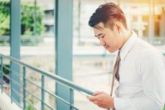Affärsman som använder minnestavlamobiltelefonen i utomhus- kontor Royaltyfri Fotografi
