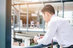 Affärsman som använder minnestavlamobiltelefonen i utomhus- kontor Fotografering för Bildbyråer