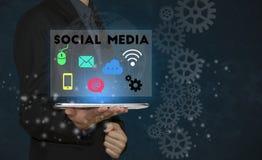 Affärsman som använder minnestavlan med socialt massmedia arkivfoton