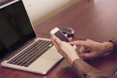 Affärsman som använder mobiltelefonen med bärbara datorn som i regeringsställning arbetar pastellfärgad signal Royaltyfri Fotografi