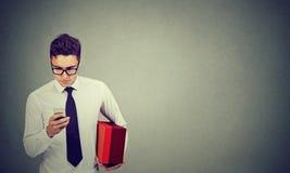 Affärsman som använder mobiltelefonen som rymmer en leveransask royaltyfri foto