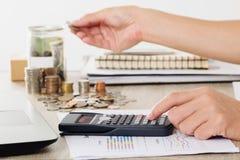 Affärsman som använder räknemaskinen på affärsdiagram, finansiell rapport med mynt och handen som sätter pengarmynt till banken Royaltyfria Bilder
