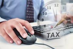 Affärsman som arbetar genom att använda datoren med sinande tid för skattpaym royaltyfri foto