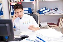 Affärsman som arbetar i kontoret med högar av böcker och legitimationshandlingar royaltyfri fotografi