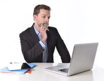 Affärsman som arbetar i spänning på eftertänksamt för bärbar dator för dator för kontorsskrivbord reflexiv och tvivelaktigt och f Arkivfoton