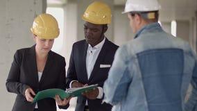 Affärsman som arbetar med arkitekten Engineer i byggnadskonstruktionsplats med ritningen som kontrollerar plan stock video