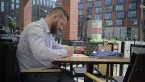 Affärsman som arbetar med minnestavlan och dokument i kafét, steadicam lager videofilmer