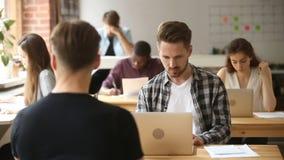 Affärsman som arbetar på bärbara datorn i coworking utrymme med mång--person som tillhör en etnisk minoritet businesspeople lager videofilmer