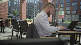 Affärsman som arbetar på bärbara datorn i kafét, steadicam lager videofilmer