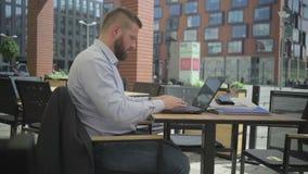 Affärsman som arbetar på bärbara datorn i kafét, steadicam arkivfilmer
