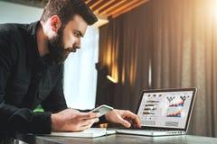 Affärsman som arbetar på bärbara datorn, medan rymma smartphonen Entreprenören analyserar information, framkallar affärsstrategi Royaltyfri Foto