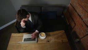 Affärsman som arbetar på bärbara datorn och dricker kaffe på kafét Top beskådar arkivfilmer