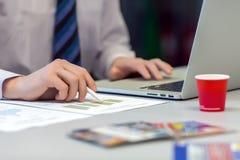 Affärsman som arbetar på bärbara datorn och utskrivavna diagram Arkivfoton