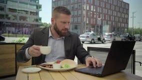 Affärsman som arbetar på bärbara datorn under lunch, steadicam arkivfilmer