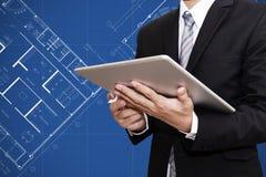 Affärsman som arbetar på den digitala minnestavlan med arkitektonisk bakgrund för ritningplanteckning, arkitekt, fastighetaffärsc arkivfoton