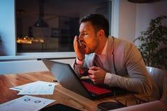 Affärsman som arbetar på en bärbar dator som överanstränger, under tryck arkivbild