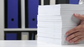 Affärsman som arbetar på ett kontor och staplar böcker arkivfilmer