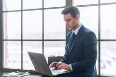 Affärsman som arbetar på hans bärbar datordator som i regeringsställning sitter arkivbild