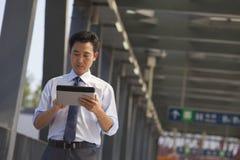 affärsman som arbetar på hans digitala minnestavla nära gångtunnelstationen Arkivbild