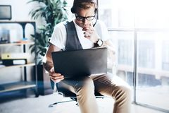 Affärsman som arbetar på hans digitala minnestavlainnehav i händer Elegant man som bär den ljudsignal hörlurar med mikrofon och g royaltyfri bild