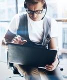 Affärsman som arbetar på hans digitala minnestavlainnehav i händer Elegant man som bär den ljudsignal hörlurar med mikrofon och g Royaltyfri Fotografi