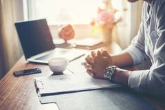 Affärsman som arbetar på hans skrivbord med en kopp kaffe på kontoret arkivbilder