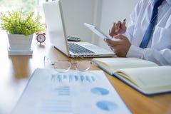 Affärsman som arbetar på kontoret med den digitala minnestavlan och dokument arkivbild