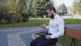Affärsman som arbetar på minnestavlan och utomhus dricker ett kaffe på bänken 4K lager videofilmer