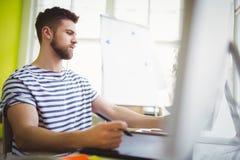 Affärsman som arbetar på skrivbordet i idérikt kontor Arkivbild