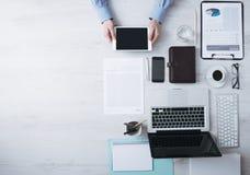 Affärsman som arbetar på skrivbordet med en digital minnestavla royaltyfria bilder