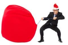 Affärsman som bär en tung gåvasäck med julhatten Arkivfoto