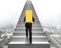 Affärsman som bär guld- guldtacka på trappa med stads- plats Fotografering för Bildbyråer