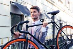 Affärsman som bär hans cykel royaltyfri bild