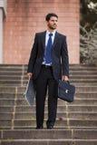 Affärsman som bär hans skateboard royaltyfri bild