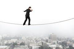Affärsman som balanserar och går på repet med stads- plats Arkivfoto
